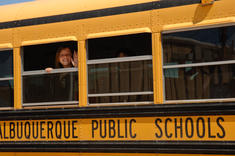 An APS student waves from inside a school bus.
